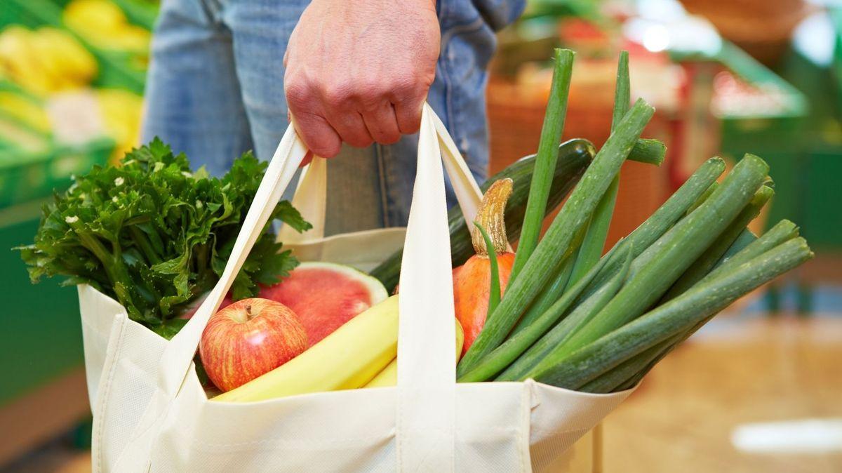 Ein Mensch trägt eine Einkaufstasche, die mit Obst und Gemüse gefüllt ist.