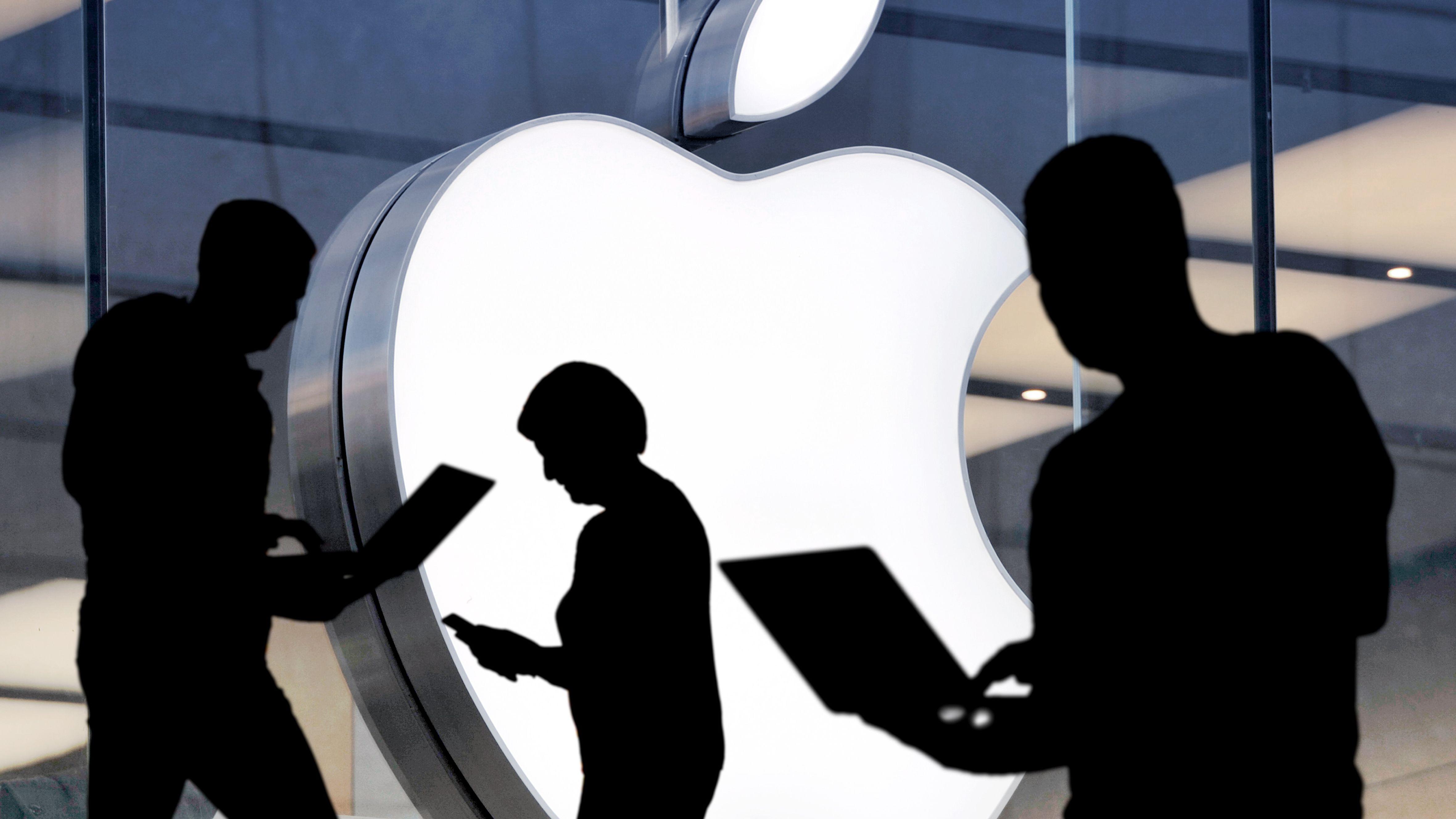 Menschen als Silhouetten arbeiten an mobilen Endgeräten vor dem Logo von Apple