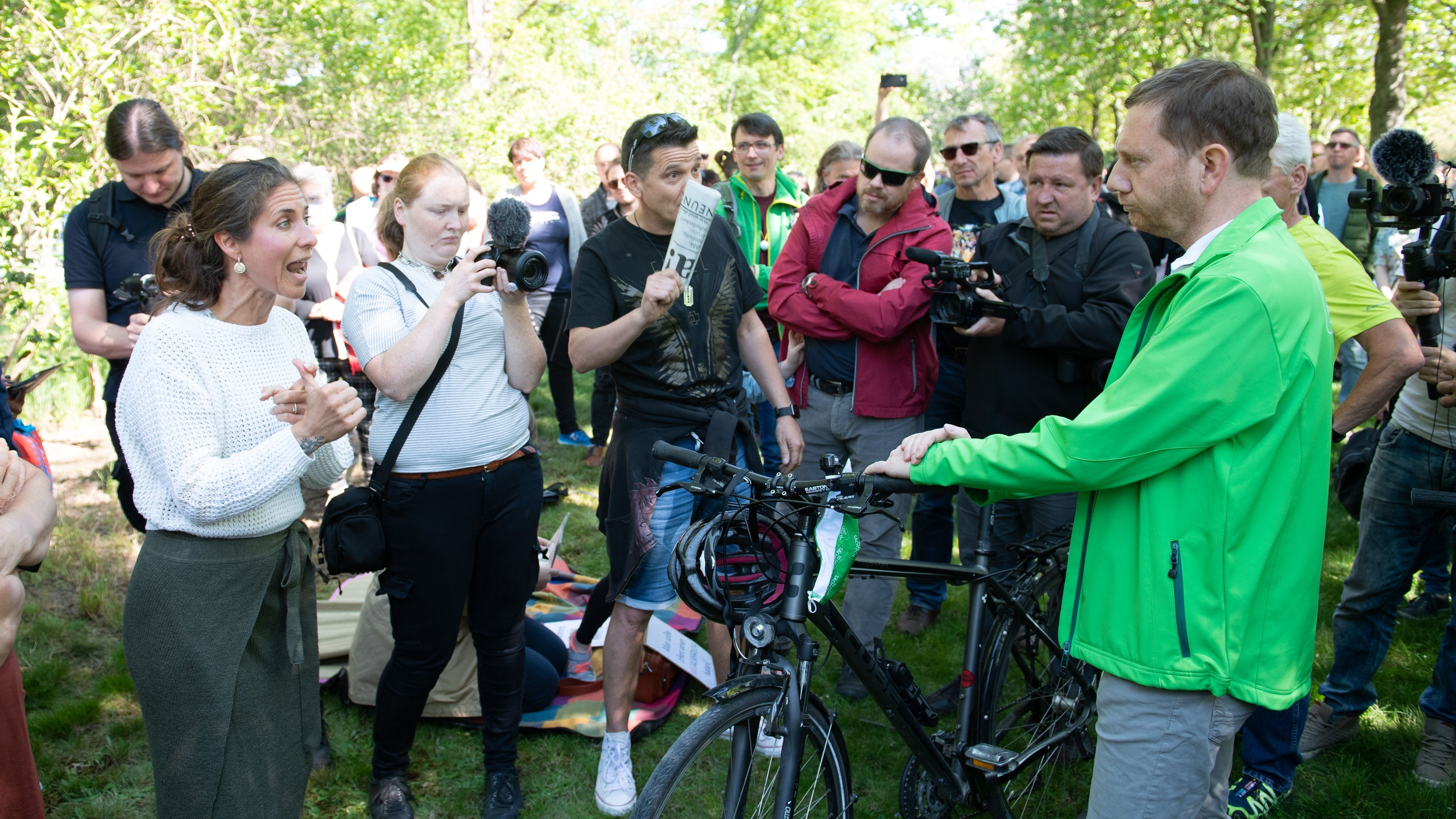 Sachsens Ministerpräsident Kretschmer (rechts im Bild) stellt sich im Großen Garten in Dresden Anhängern von Verschwörungstheorien.