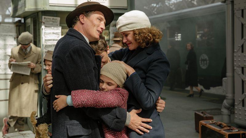 """Szenenfoto aus """"Als Hitler das rosa Kaninchen stahl"""": Eltern und Kinder der Familie Kerr umarmen sich auf einem Bahnhof, im Hintergrund ein Zug der 40er-Jahre"""