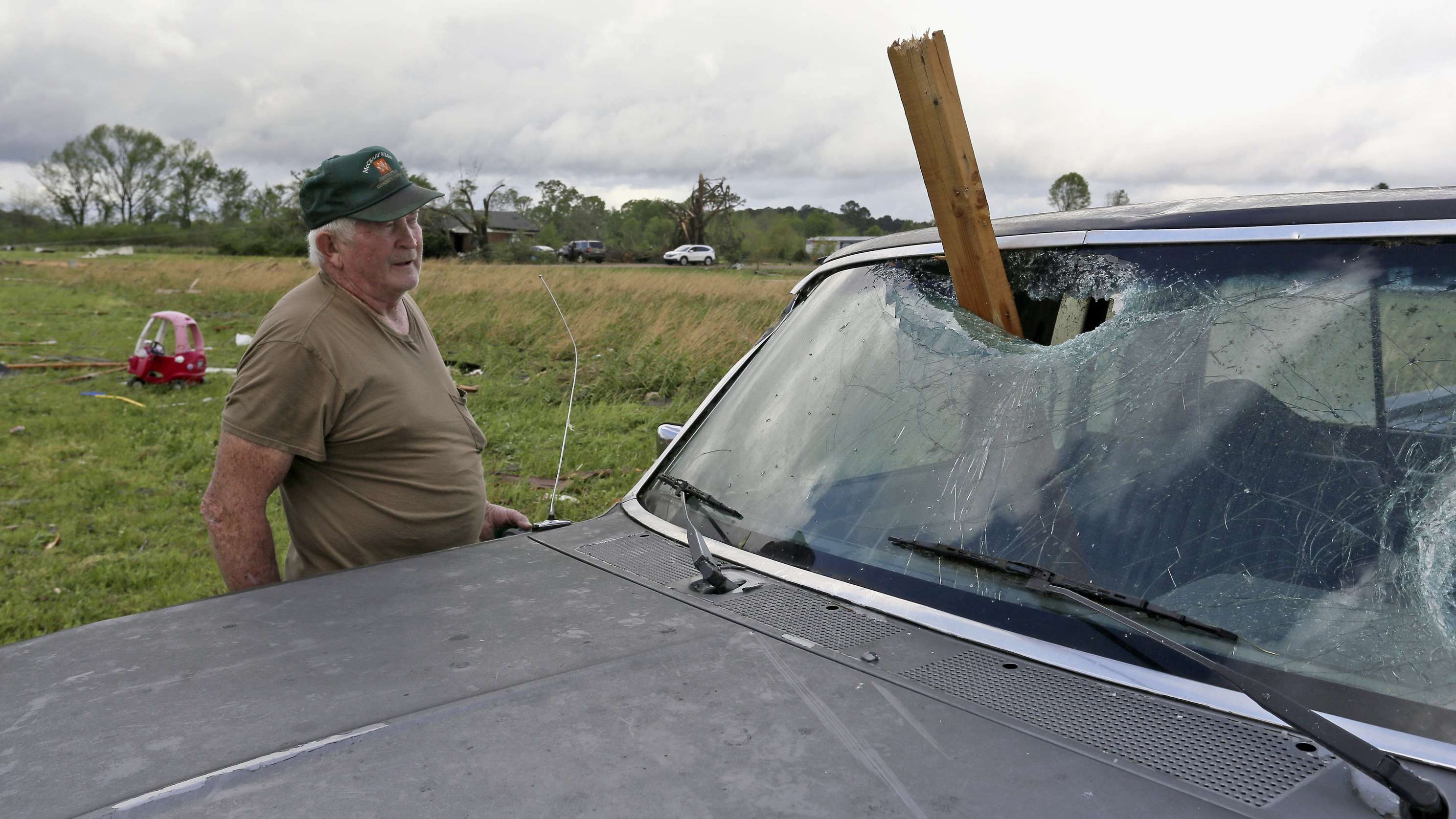 Ein Mann schaut auf sein vom Tornado zerstörtes Auto: Ein Holzbalken hat die Windschutzscheibe durchschlagen.