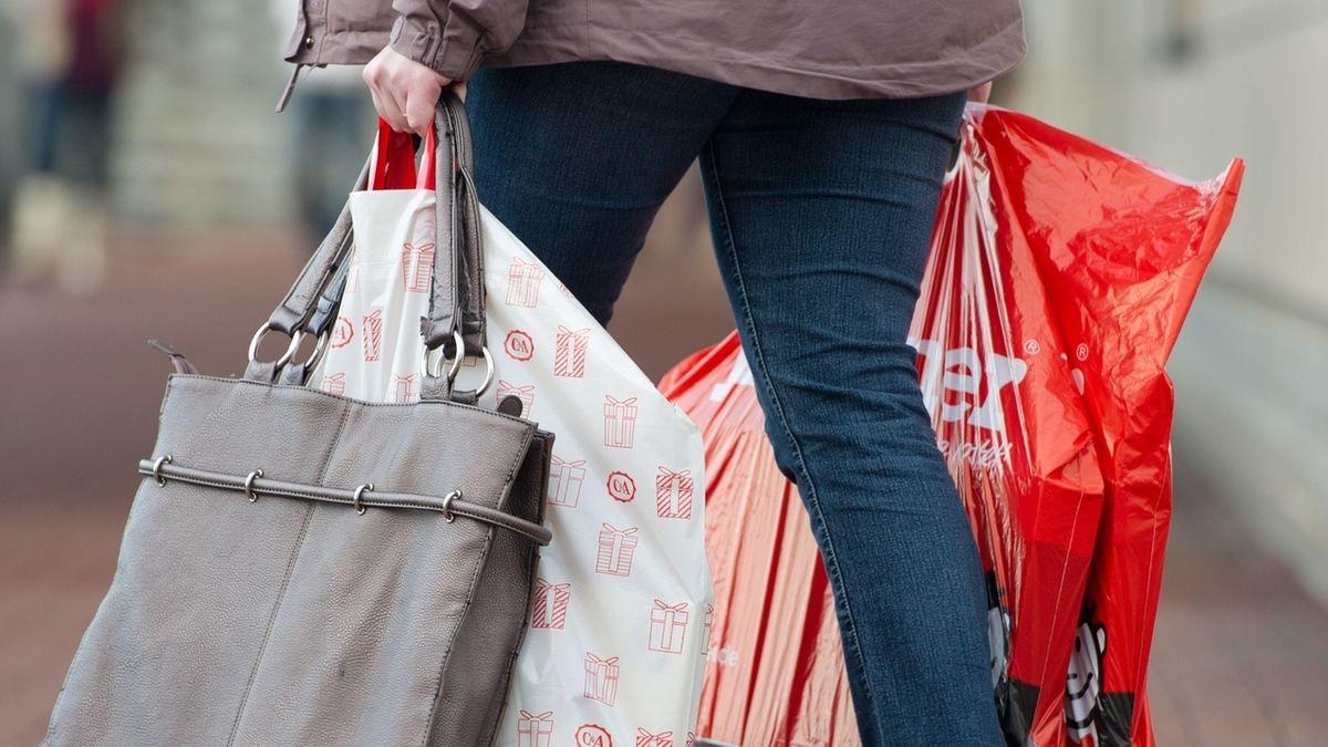 Frau trägt mehrere Einkaufstüten