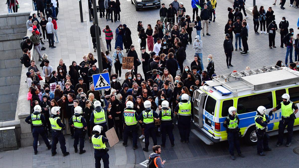 Mehrere Dutzend Demonstranten stehen dicht bei einander. Vor ihnen ein Dutzend Polizisten und ein Polizeifahrzeug.