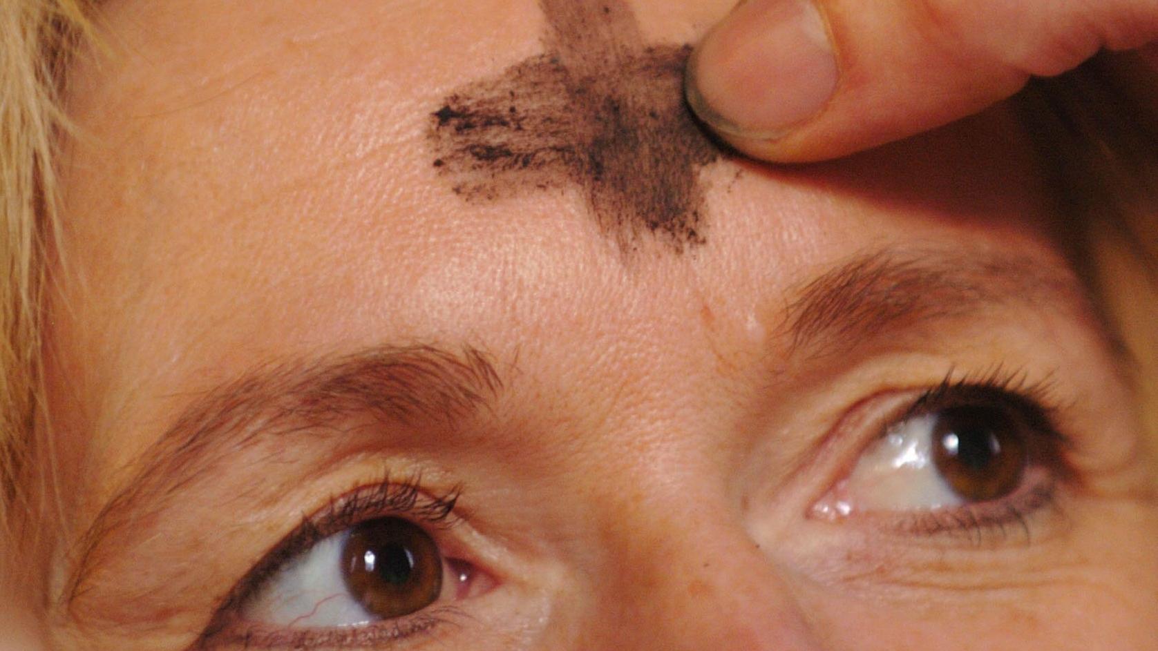 Ein Priester zeichnet ein Aschekreuz auf die Stirn einer Gläubigen.