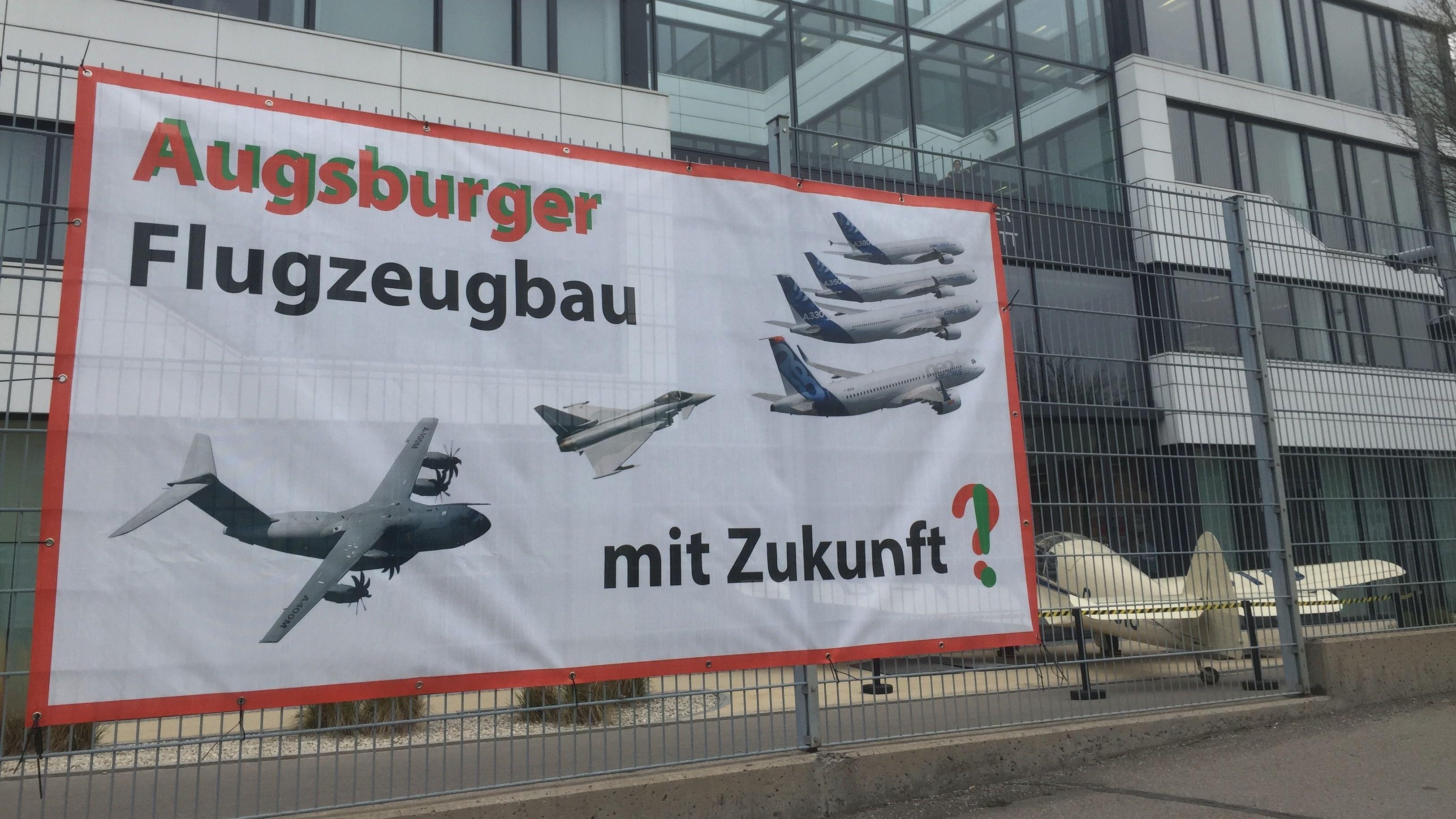 Plakat am Zaun der Premium Aerotec in Augsburg.
