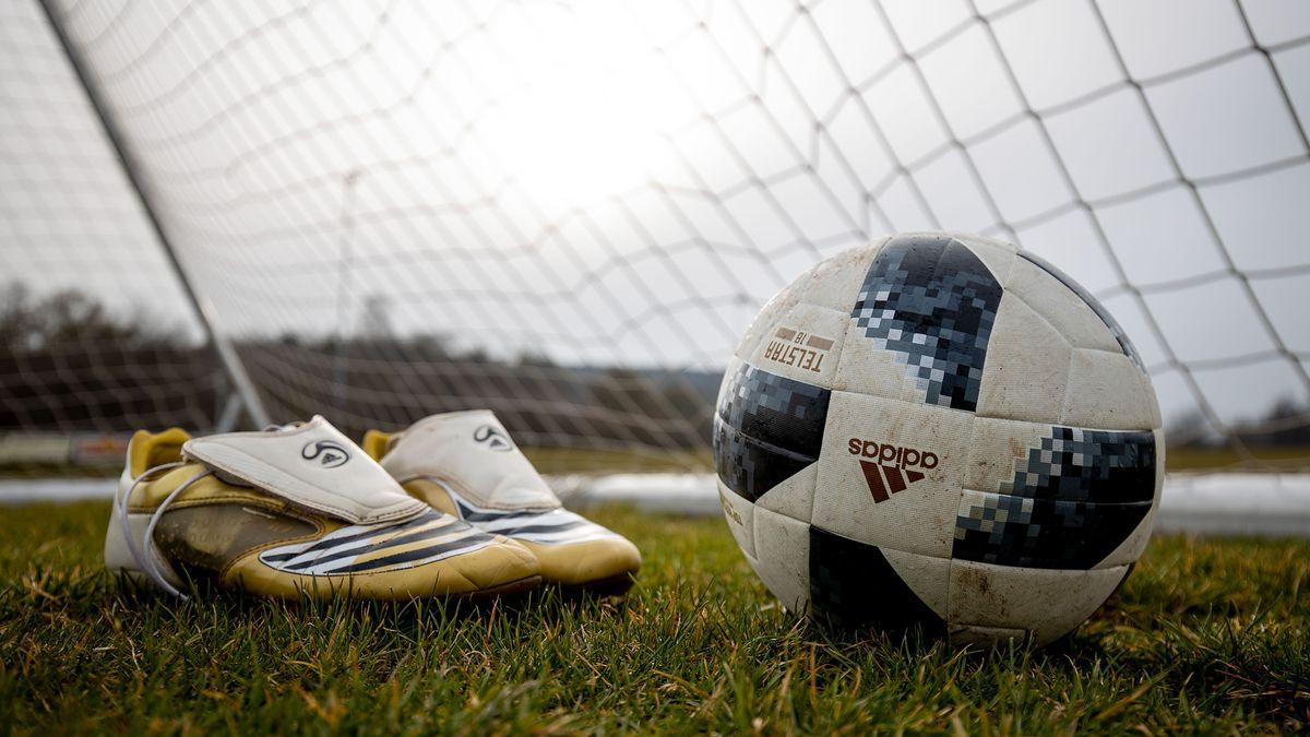 Fußballschuhe und ein Ball stehen vor einem Tor (Symbolbild)