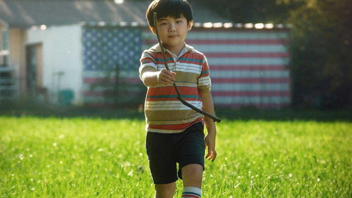 Ein koreanischer Junge geht mit einem Stock in der Hand über eine Wiese. Im Hintergrund ist eine US-Flagge an einer Hauswand zu sehen.