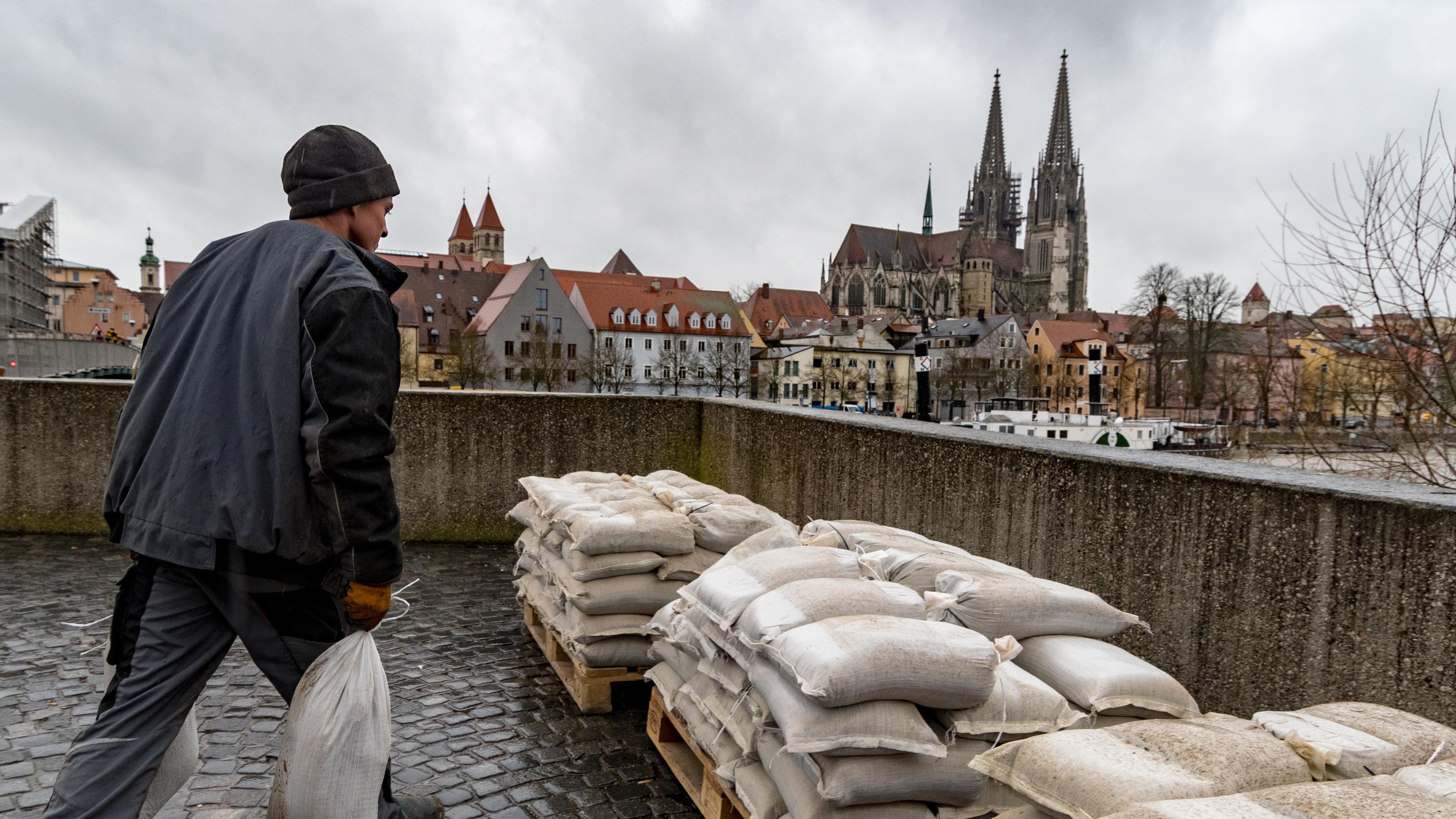 Ein Mann trägt am 04.01.2018 am Ufer der Donau in Regensburg Sandsäcke.
