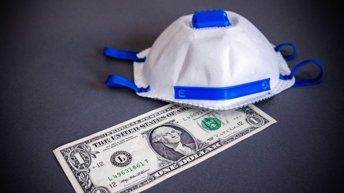 Eine Atemschutzmaske liegt auf auf einer Dollarnote - Symbolbild