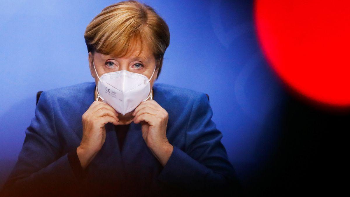 """28.10.2020, Berlin: Bundeskanzlerin Angela Merkel (CDU)setzt am Ende einer Pressekonferenz, nach einem Treffen mit den Ministerpräsidenten der Länder zum weiteren Vorgehen in der Corona-Pandemie, ihre Maske auf. (Zu dpa """"Merkel zum Teil-Lockdown:Wollen schnell und unbürokratisch helfen"""") Foto: Fabrizio Bensch/Reuters Pool/dpa +++ dpa-Bildfunk +++"""
