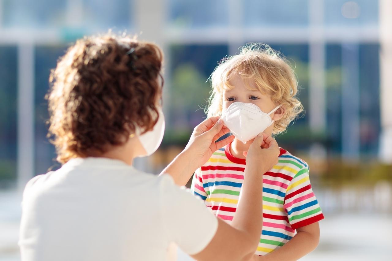 Eine Mutter zieht ihrem Sohn einen Mundschutz an.