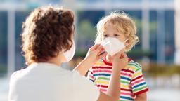 Eine Mutter zieht ihrem Sohn einen Mundschutz an. | Bild:stock.adobe.com/famveldman