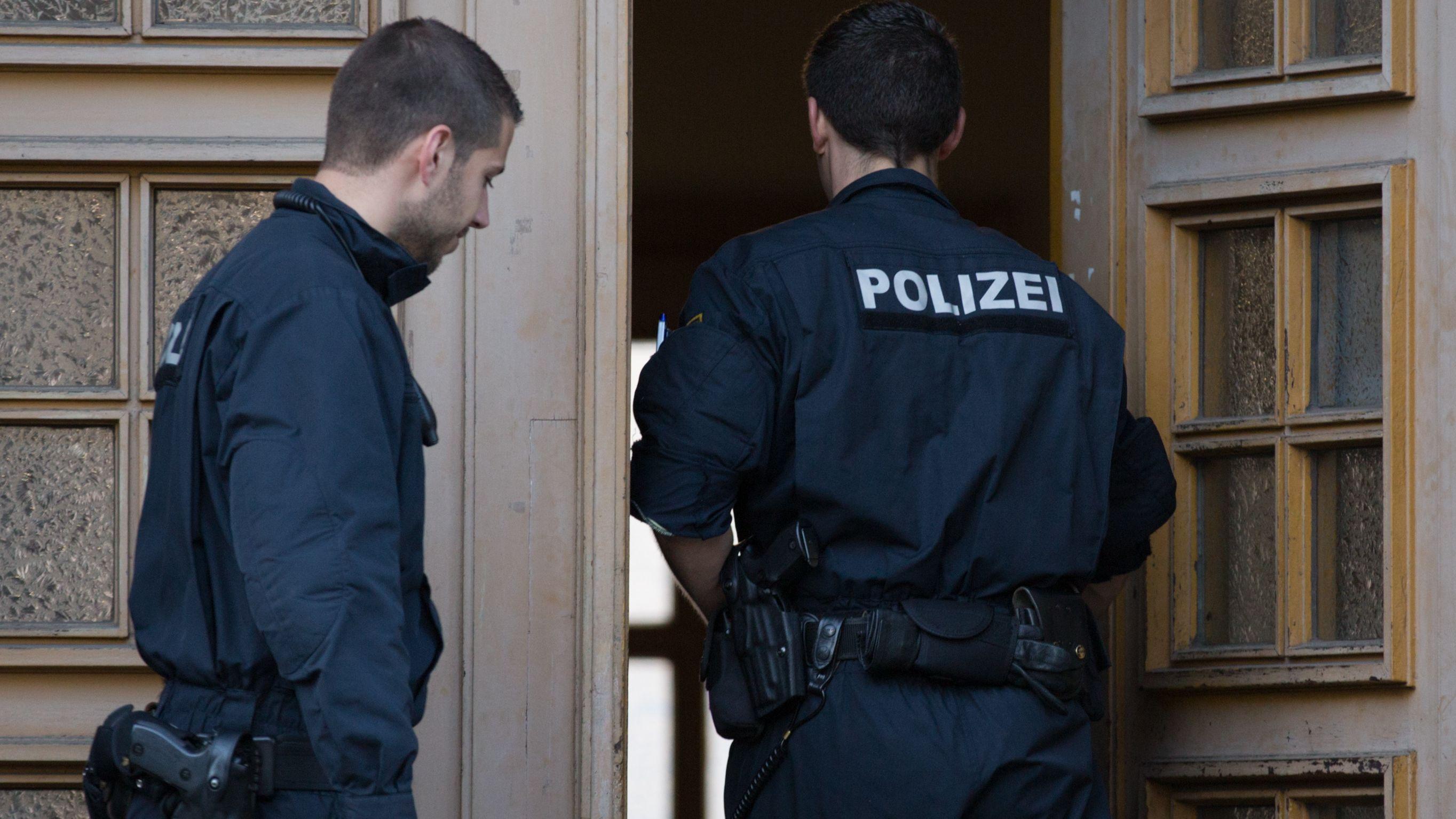 Zwei Polizisten an einer Haustür (Symbolbild)