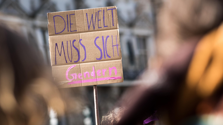 """Menschen nehmen an einer Demonstration zum Internationalen Frauentag auf dem Rathausmarkt teil. Ein Schild zeigt die Aufschrift: """"Die Welt muss sich gendern."""""""