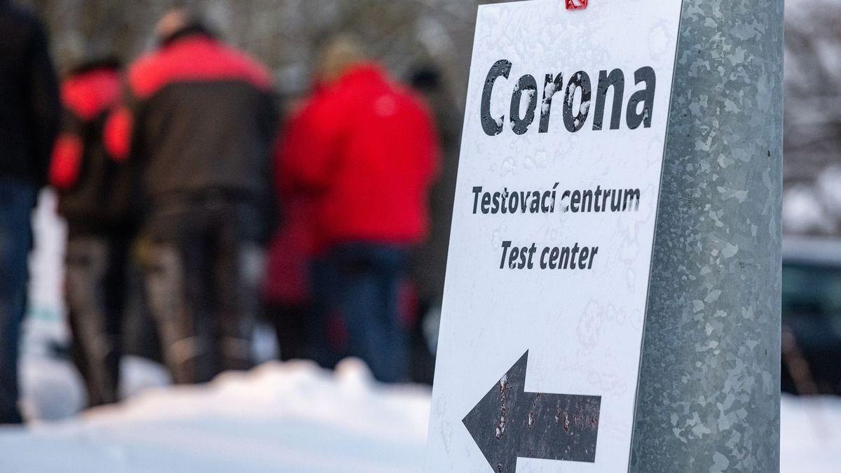 Menschen stehen im Schnee vor einem Corona-Testzentrum an