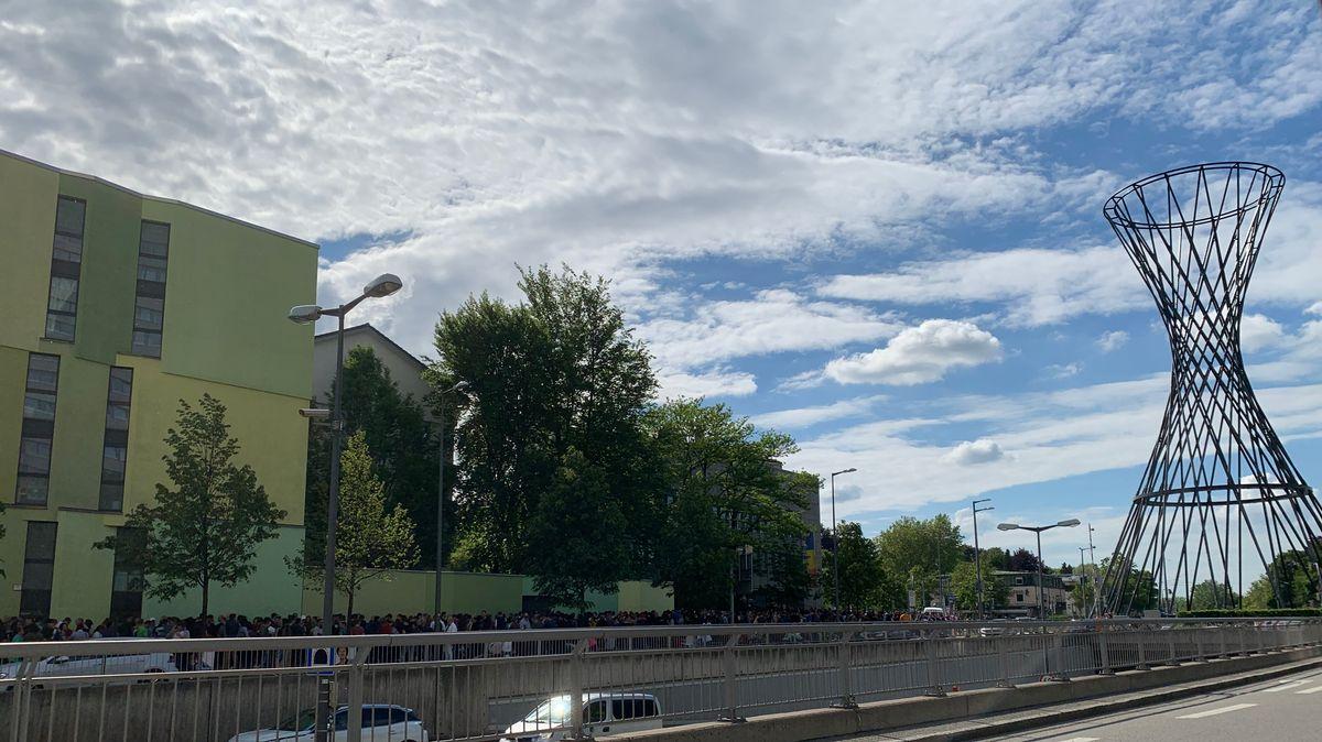 Menschen warten vor dem rumänischen Konsulat am Effnerplatz in München.