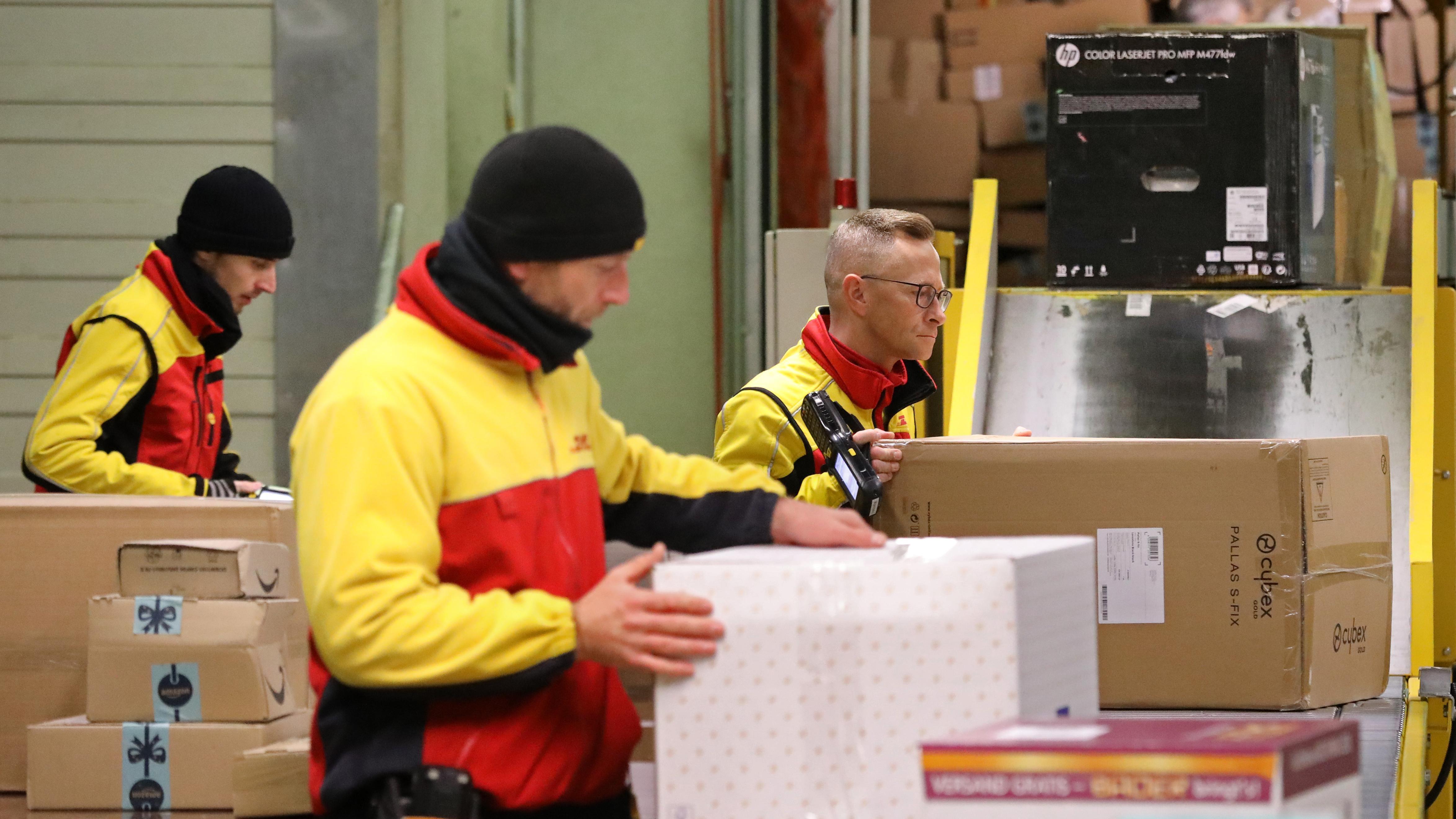 Vor einem Fließband sortieren Mitarbeiter der Deutschen Post DHL Pakete