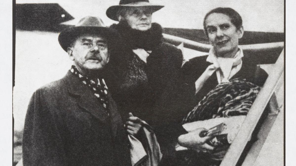 Schwarz-weiß-Foto: Thomas, Katia und Erika Mann, New York, 1949, stehen mit Gepäck auf der Flugzeugtreppe.