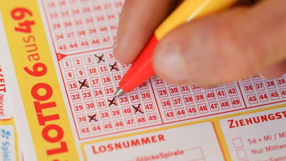 Jemand füllt mit einem Kugelschreiber einen Lottoschein aus.