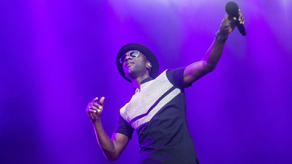 Der Musiker Aloe Blacc hält in der linken Hand sein Mikro in die Luft, auf dem Kopf: Hut und Sonnenbrille.