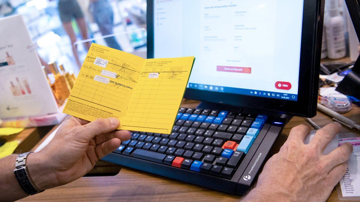 Ein Apotheker stellt am Computer einen digitalen Impfnachweis aus.