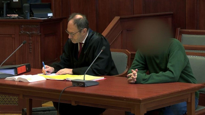 Der Angeklagte im grünen Pullover sitzt auf der Anklagebank, daneben sein Verteidiger in der schwarzen Anwaltsrobe.