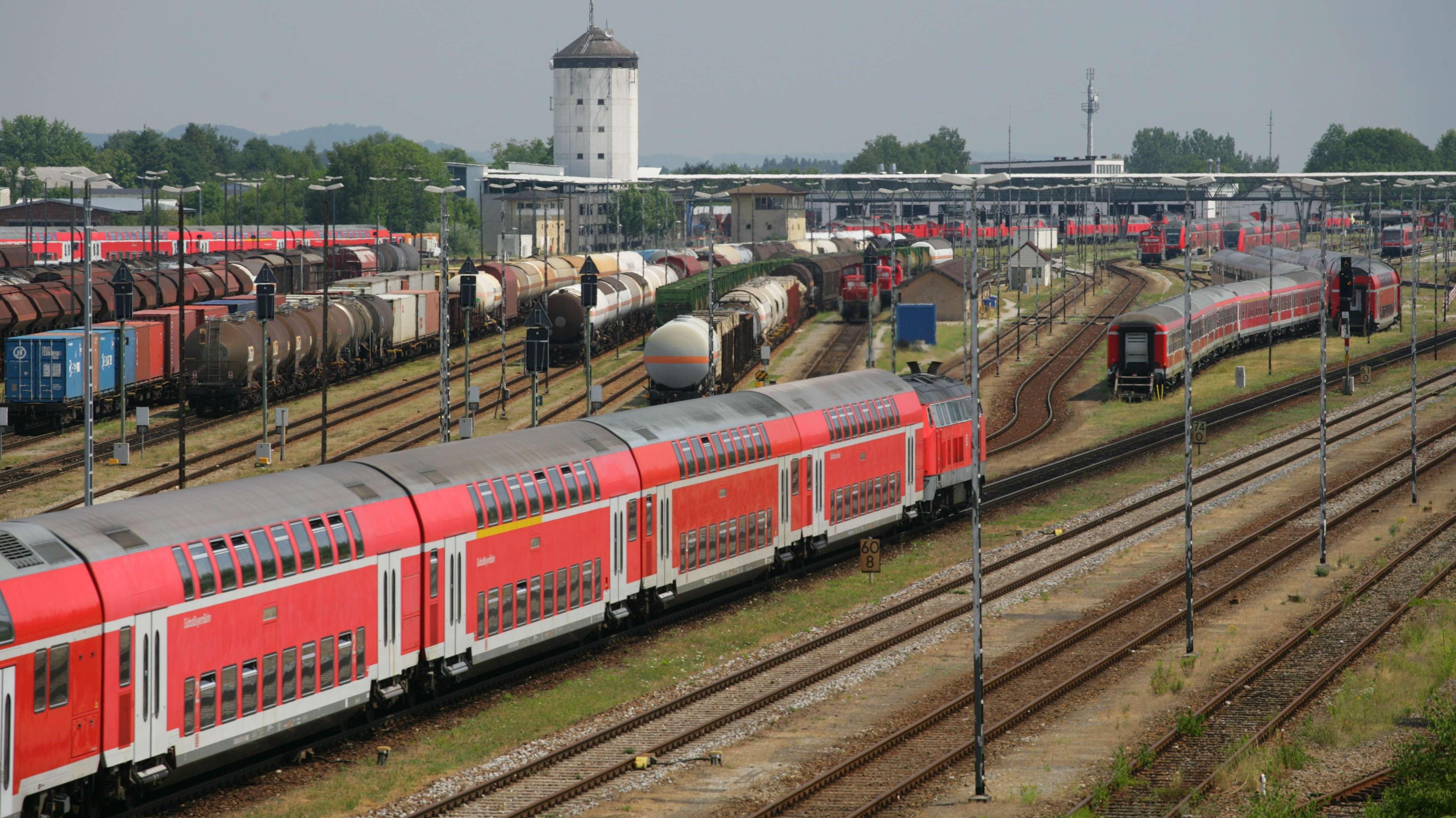 Gleisfeld mit Personenzug mit Güterzügen, vor dem Bahnhof in Mühldorf am Inn.