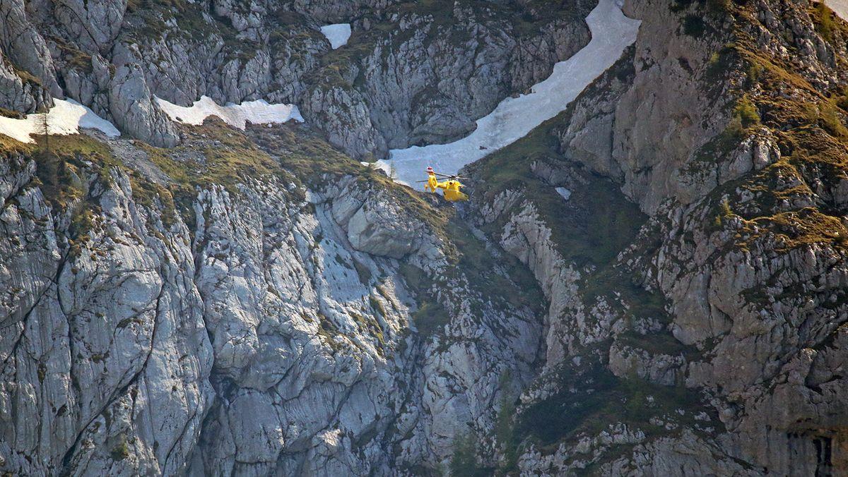 """Der Salzburger Notarzthubschraubers """"Christophorus 6"""" an der Nordostseite des Hohen Göll; im Hintergrund Schneefelder auf der Schusterroute."""