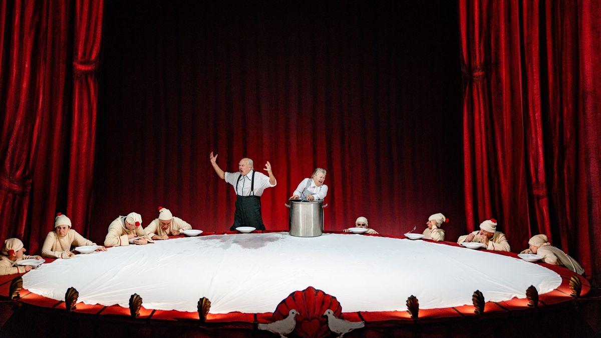 """Auf einer Bühne mit roten Vorhängen steht ein überdimensioniertes tischähnliches Gebilde um das Schauspieler sitzen - Szene aus """"Der deutsche Mittagstisch"""""""