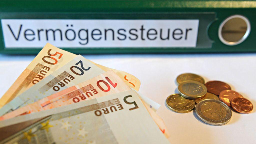 """Ein Ordner mit der Aufschrift """"Vermögenssteuer"""" liegt hinter Geldmünzen und Geldscheinen"""