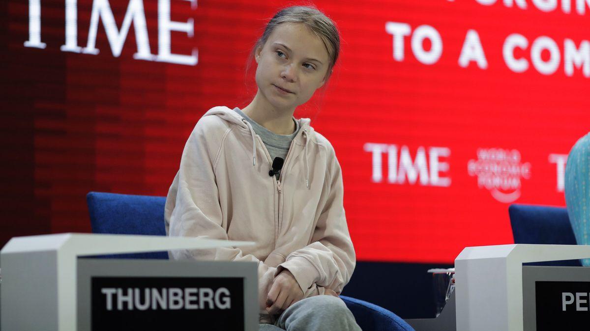 """Greta Thunberg, Umweltaktivistin und Schülerin aus Schweden, sitzt auf dem Podium, im Hintergrund eine rot beleuchtete Tafel mit der Aufschrift """"Time""""."""