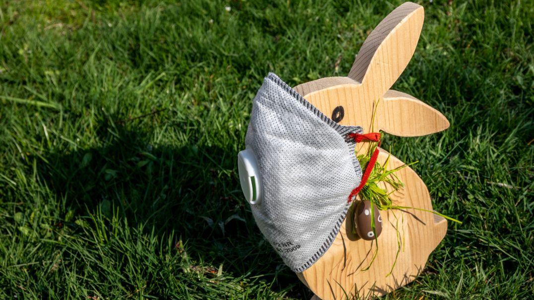 Ein Osterhase aus Holz steht auf einer Wiese und trägt eine FFP-Maske mit Filter.
