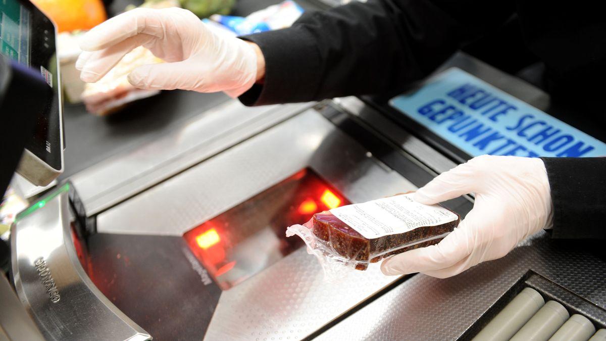Eine Kassiererin mit Schutzhandschuhen bei der Arbeit in einer Supermarkt-Filiale