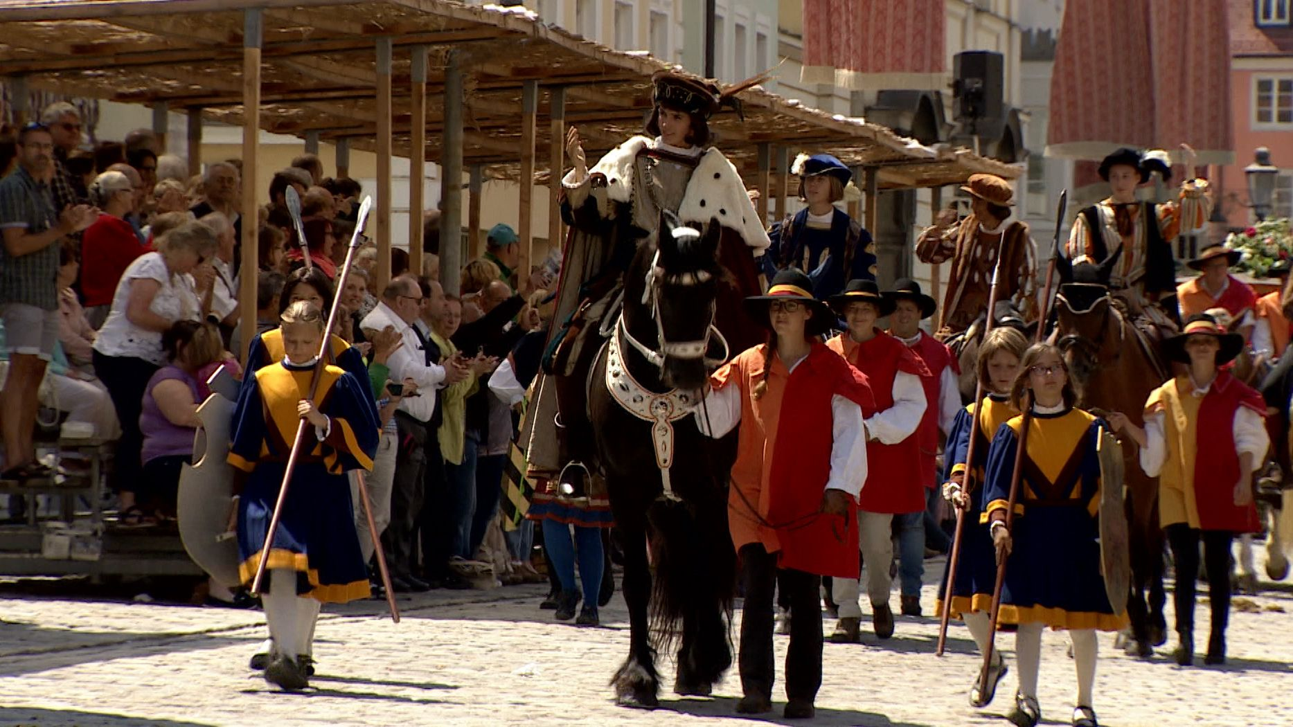 Kinder in historischen Gewändern spielen Geschichte Kaufbeurens nach.