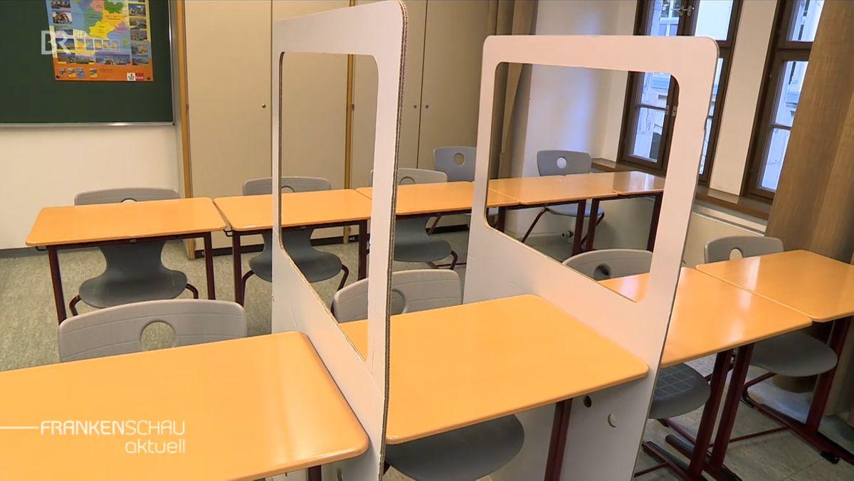 Stellwände aus Pappe mit einem Fenstern trennen die Schüler, die auf den Sitzen, voneinander.