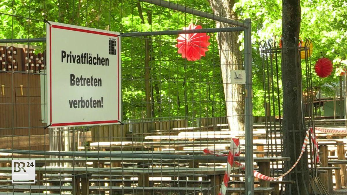 Bauzaun und Flatterband sperren leere Bierbänke und -tische auf einem Keller der Bergkirchweih in Erlangen ab.