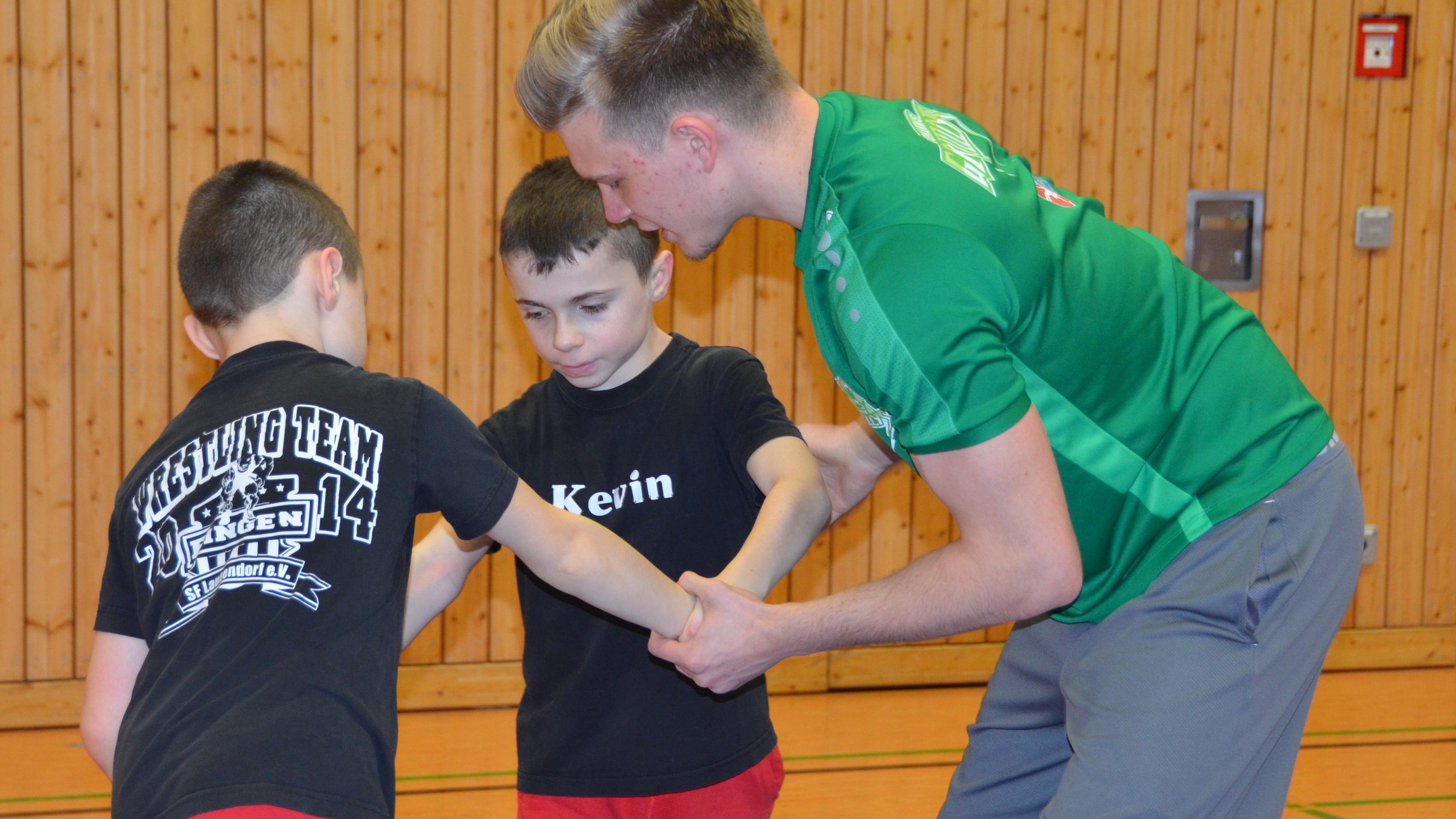 Ringer Nico Sausenthaler (r.) mit den Nachwuchssportlern Bryan und Kevin