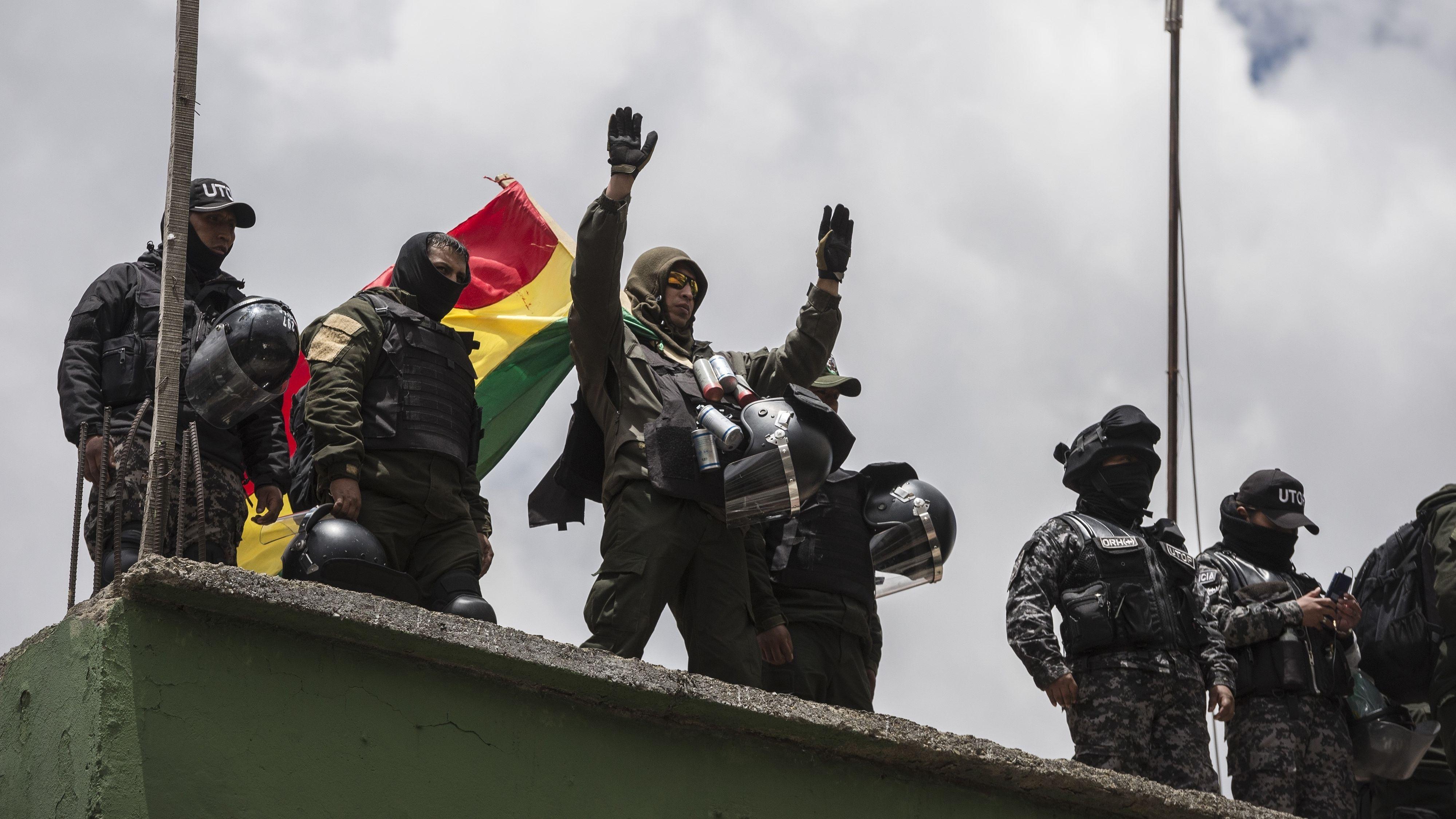 Polizisten grüßen Demonstranten vom Dach einer Polizeistation in La Paz, Bolivien.