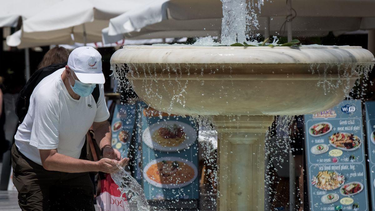 Mann kühlt sich an einem Brunnen ab in Chania, Griechenland