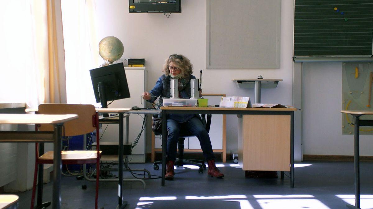 Lehrerin Theresia Friedl-Schneider sitzt in ihrem leeren Klassenzimmer vor dem Computer.