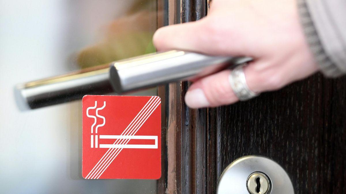 Eine Frau betritt ein Lokal mit Rauchverbot.