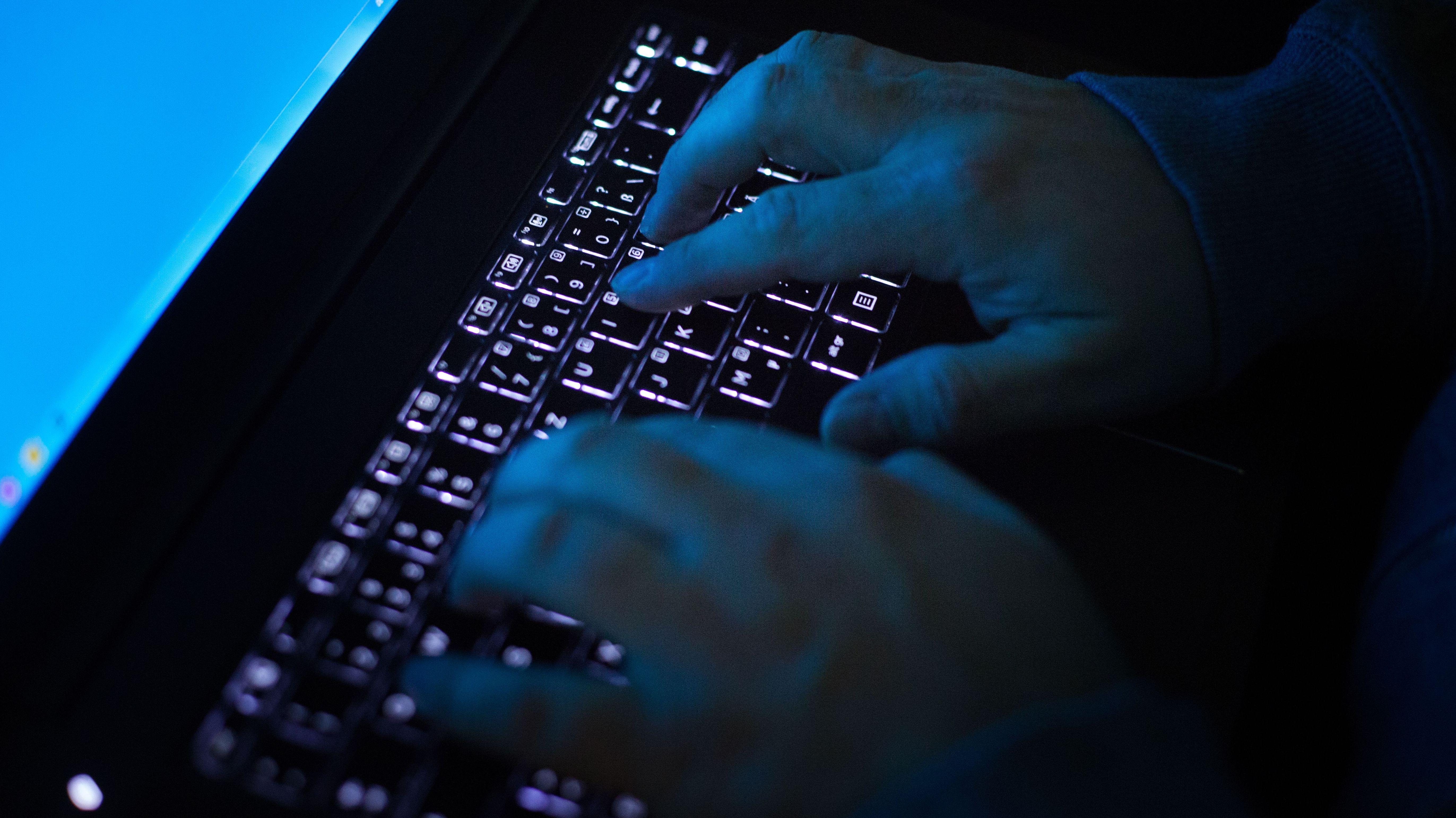 Unbekannter Mann schreibt im Dunklen auf einer Laptop-Tastatur