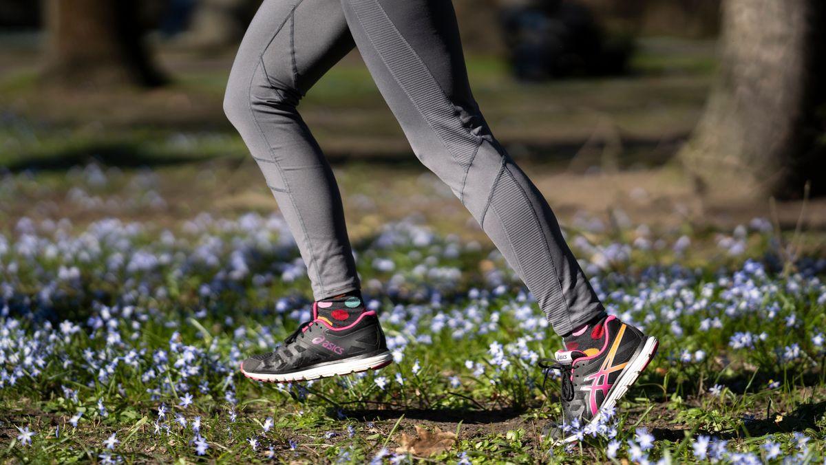 Eine Frau joggt über eine Blumenwiese (Symbolbild)