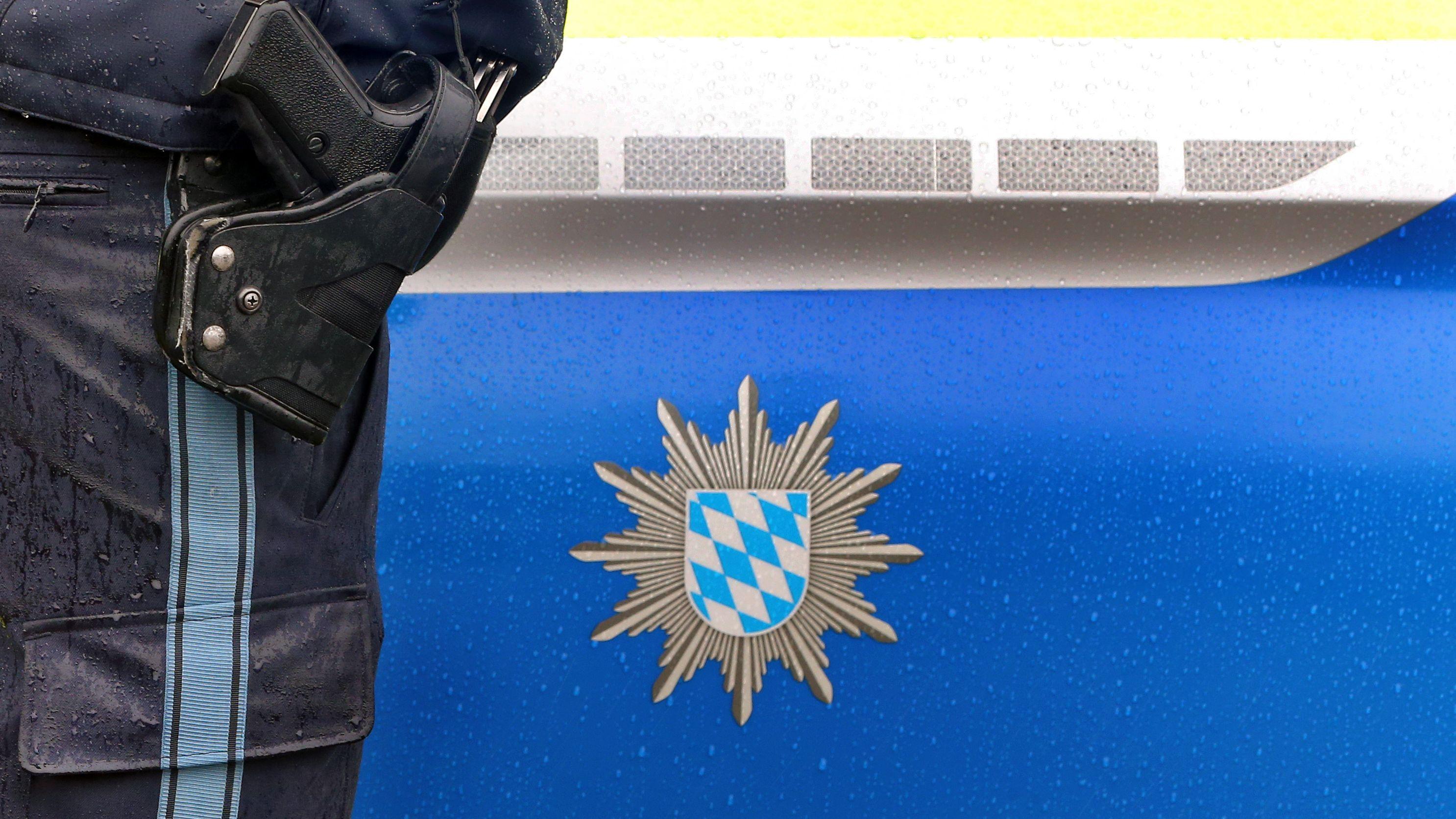 Ein bayerischer Polizist mit Handschellen und einer Pistole am Gürtel steht vor einem Streifenwagen. Symbolbild