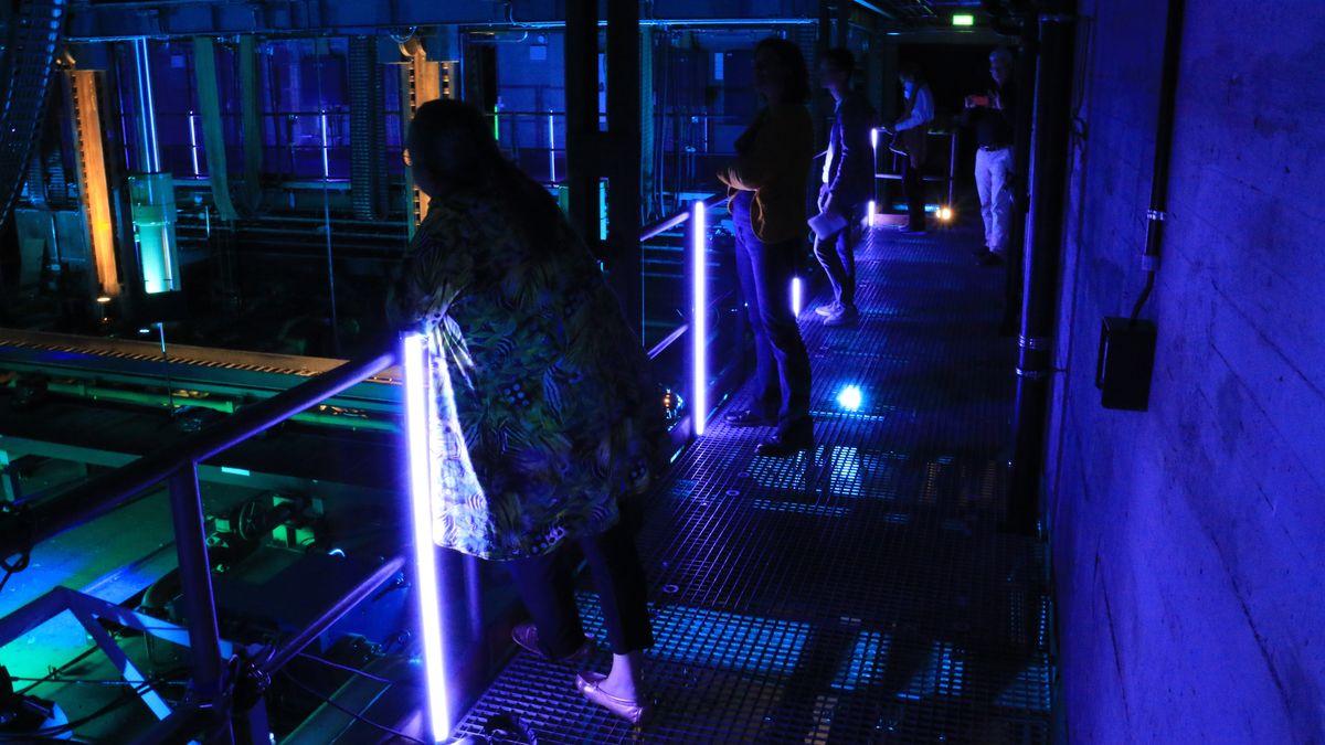 Im violetten Licht der Unterbühne stehen Zuschauer auf einer Brüstung und betrachten das Geschehen