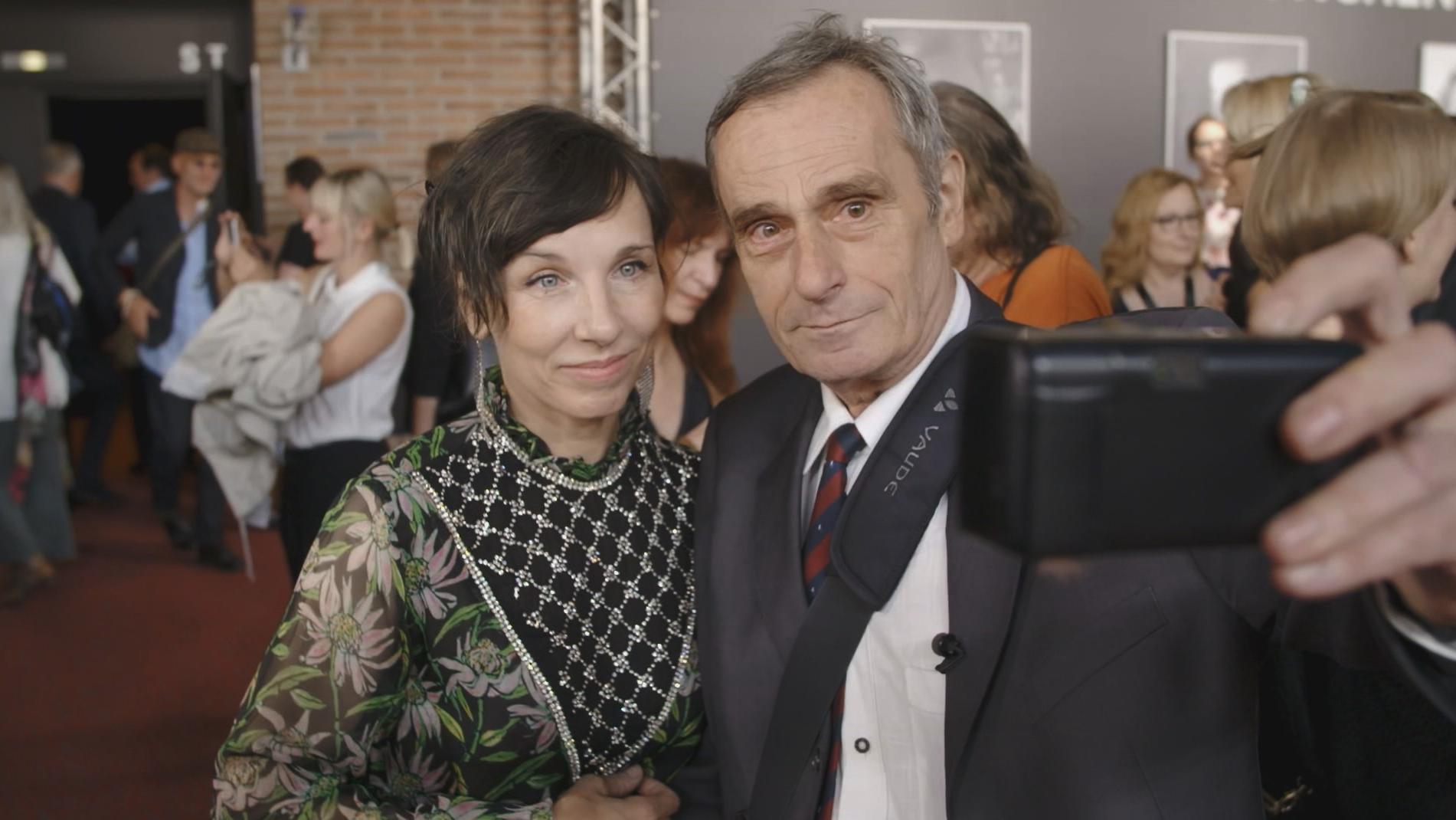 Selfie-Pionier Wolfgang Maier zusammen mit Meret Becker, in der Hand seine analoge Kleinbildkamera
