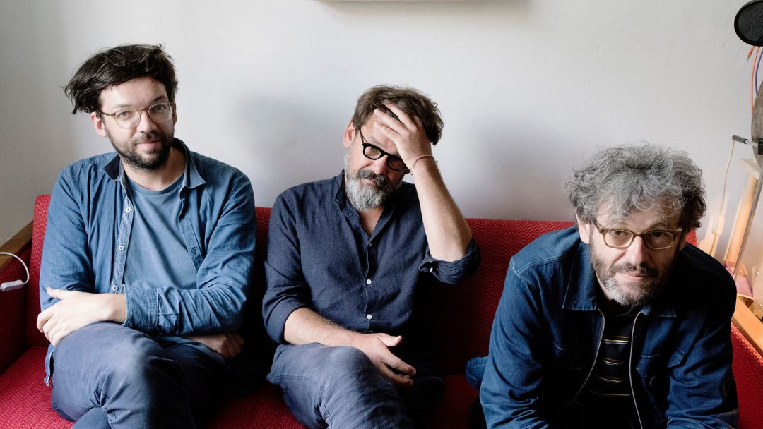 Drei blaugekeidete Männer auf einem roten Sofa