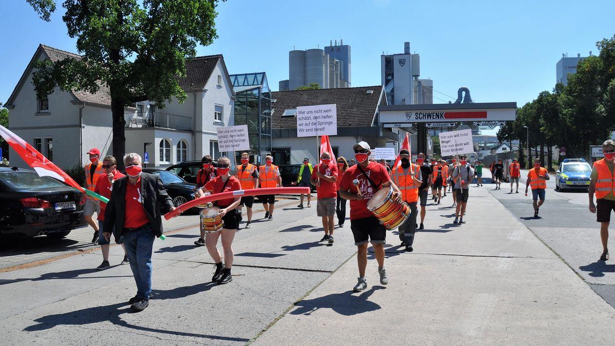Mitarbeiter des Zementwerks Schwenk in Karlstadt demonstrieren mit Trommeln, Fahnen und Plakaten - und mit Masken und Abstand