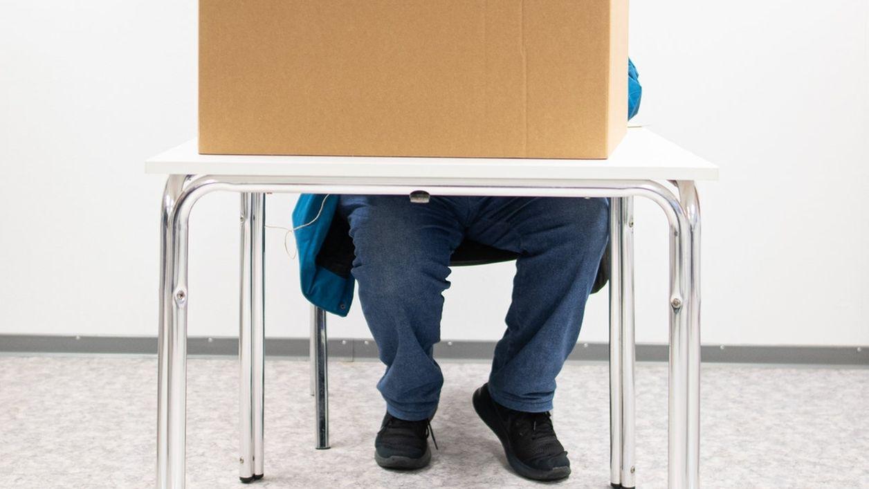 Ein Mann gibt in einer Wahlkabine seine Stimme ab (Symbolbild)
