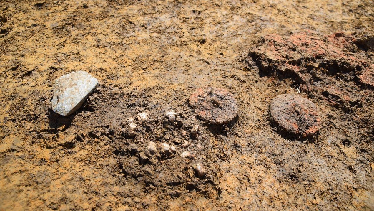 Auf einer lehmigen Erde liegen zwei Räder aus Ton